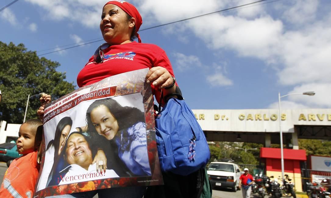 Uma mulher segura um banner com uma foto do presidente Hugo Chávez e sua filha, a primeira imagem divulgada pelo governo depois da internação do líder em dezembro passado Foto: Carlos Garcia Rawlins / REUTERS