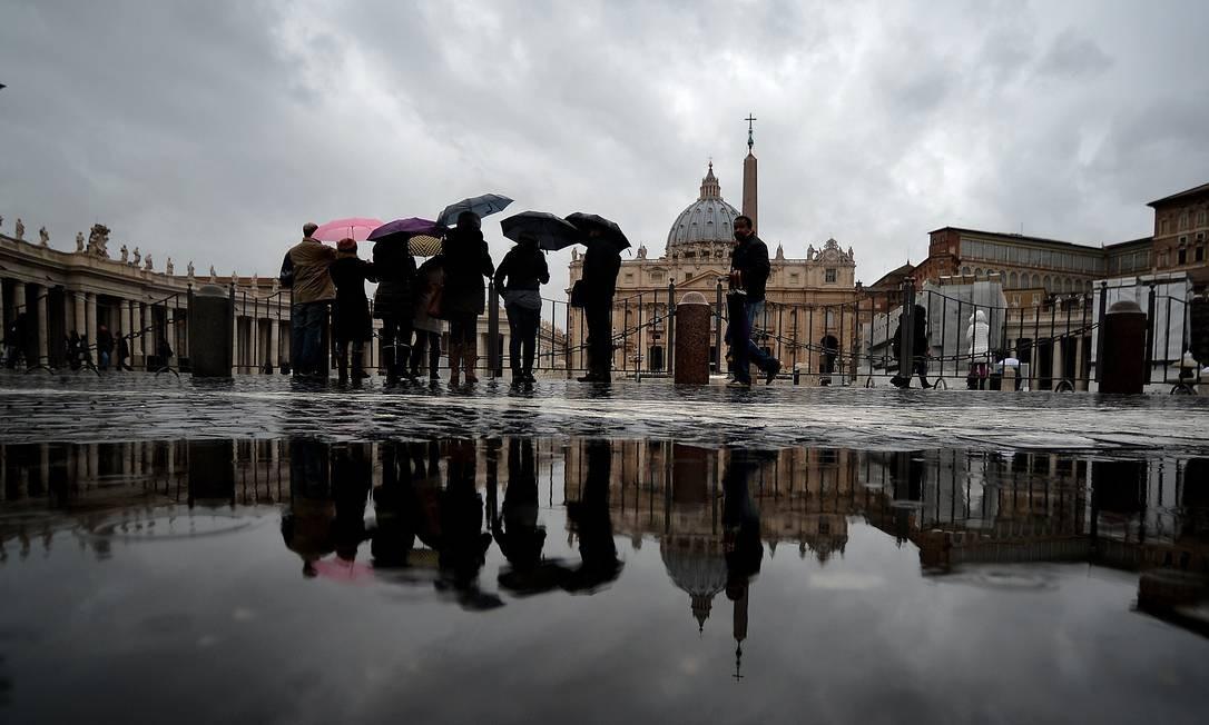 Turistas passam pela Praça de São Pedro no sábado (23), um dia antes do papa Bento XVI celebrar sua última missa do Ângelus Foto: FILIPPO MONTEFORTE / AFP