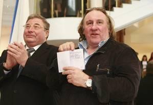 O ator Gérard Depardieu (à direita) mostra seu passaporte com autorização de residência, enquanto Vladimir Volkov, chefe da República da Mordóvia, aplaude, durante uma visita à cidade de Saransk, a sudeste de Moscou Foto: STRINGER/RUSSIA / REUTERS