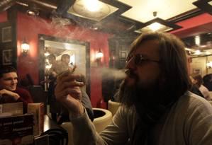 Homem fuma em um café no centro da cidade de Krasnoyarsk, na Sibéria Foto: ILYA NAYMUSHIN / REUTERS