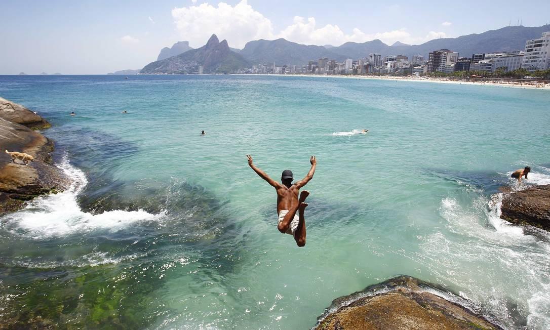 Jovem pula no mar no Arpoador Foto: Pablo Jacob / O Globo