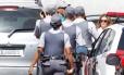 De boné e camisa verde, o torcedor do Corinthians é levado por policiais para prestar depoimento na Vara da Infância e da Juventude de Guarulhos
