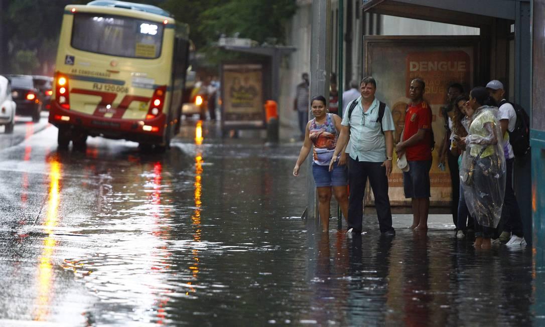 A forte chuva que atingiu o Rio prejudicou também a vida de passageiros na volta para casa, uma vez que o alagamento chegou às calçadas e pontos de ônibus; na foto, pessoas esperam coletivo na Avenida Presidente Vargas Pablo Jacob / O Globo