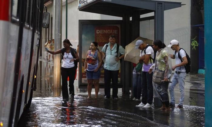 Mulher tem dificuldade para entrar em ônibus na Avenida Presidente Vargas devido a alagamento Pablo Jacob / O Globo