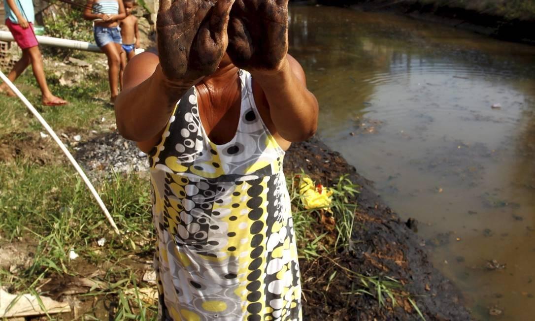 Nas mãos. Moradora de Duque de Caxias mostra a contaminação do Rio Pilar Foto: Custódio Coimbra / O Globo