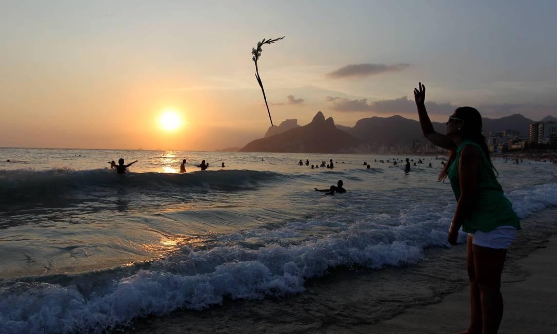 Devota de Iemanjá lança palma branca ao mar do Arpoador no último dia de 2012 Foto: Domingos Peixoto / O Globo