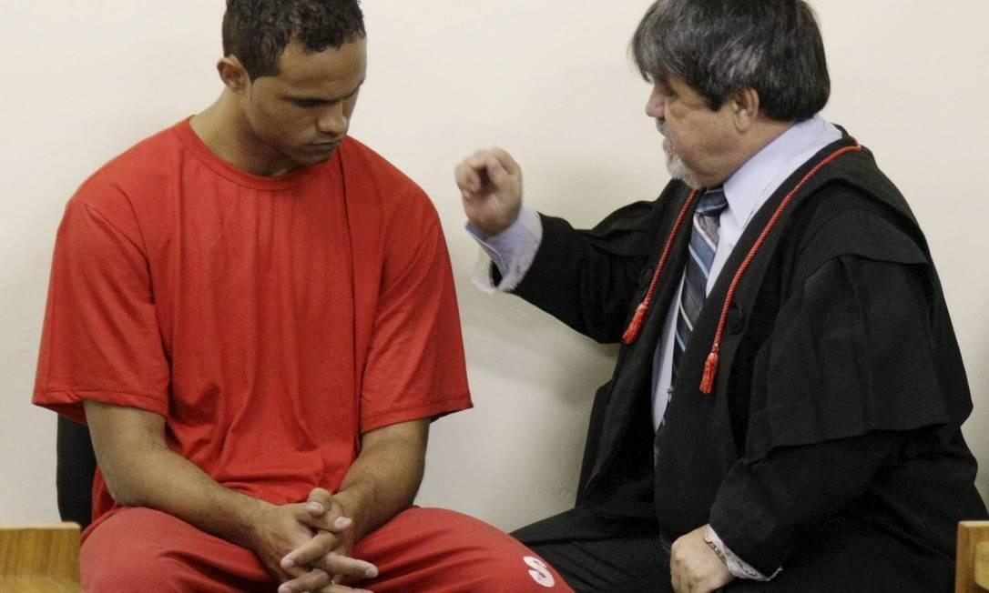 De cabeça baixa, Bruno é orientado pelo advogado Foto: Fabiano Rocha / O Globo