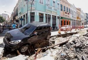 Rastro de destruição na quarta-feira: carro cai em buraco de obra na Rua dos Inválidos, no Centro Foto: Pedro Kirilos / Agência O Globo