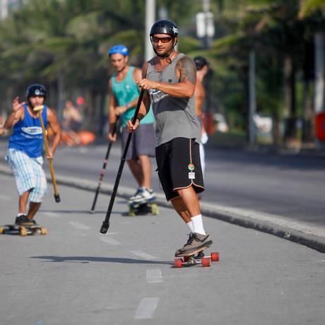 Remando na ciclovia. Gabriel pratica o skate paddle com um colega em Ipanema Foto: Pedro Kirilos / O Globo