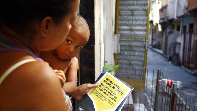 Novos tempos. A dona de casa Célia do Rosário com o folheto que detalha os diretos dos moradores da Maré Foto: Pablo Jacob / O Globo