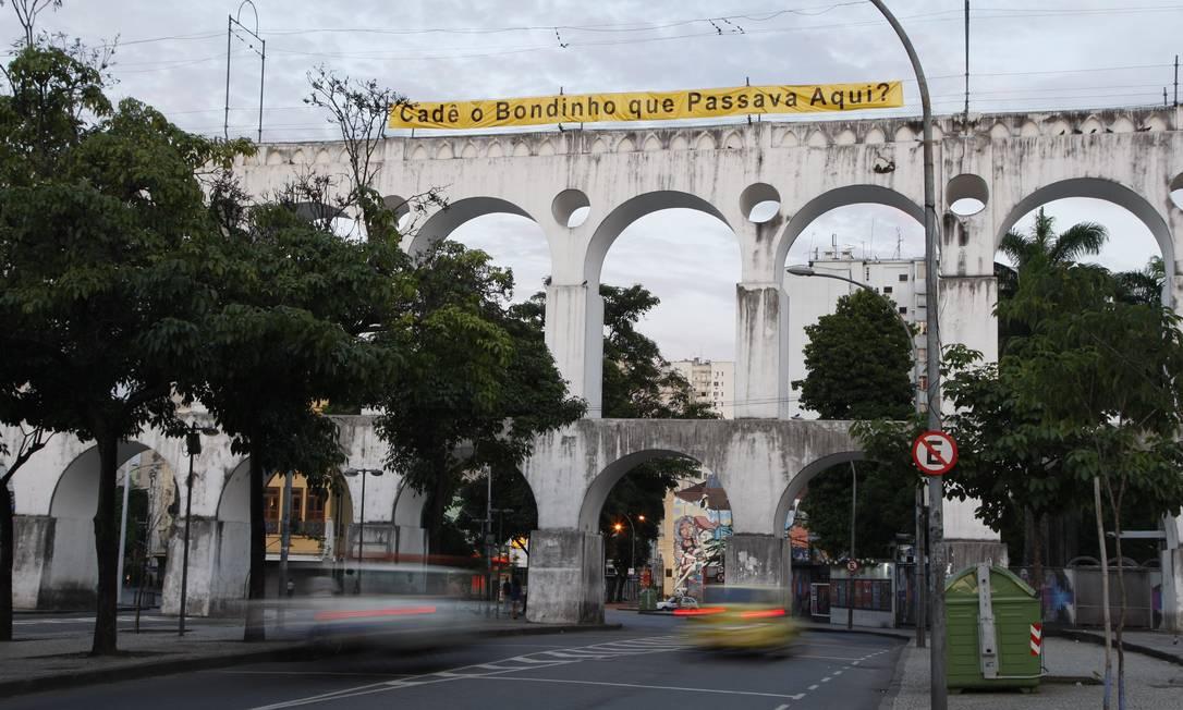 Faixa em protesto contra demora na retomada do serviço de bondes é colocada nos Arcos da Lapa Foto: Marcos Tristão / O Globo