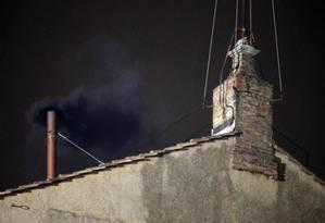 Fumaça preta sai da chaminé da Capela Sistina, indicando que primeira votação acabou sem eleger um novo Papa Foto: Gregorio Borgia / AP