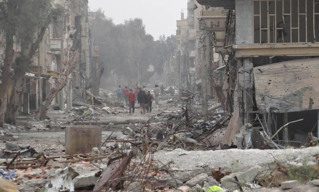 Pessoas andam em uma rua destruída por um avião de caça da Força Aérea leal ao presidente Bashar al-Assad, em Deir Al-Zor Foto: HANDOUT / REUTERS
