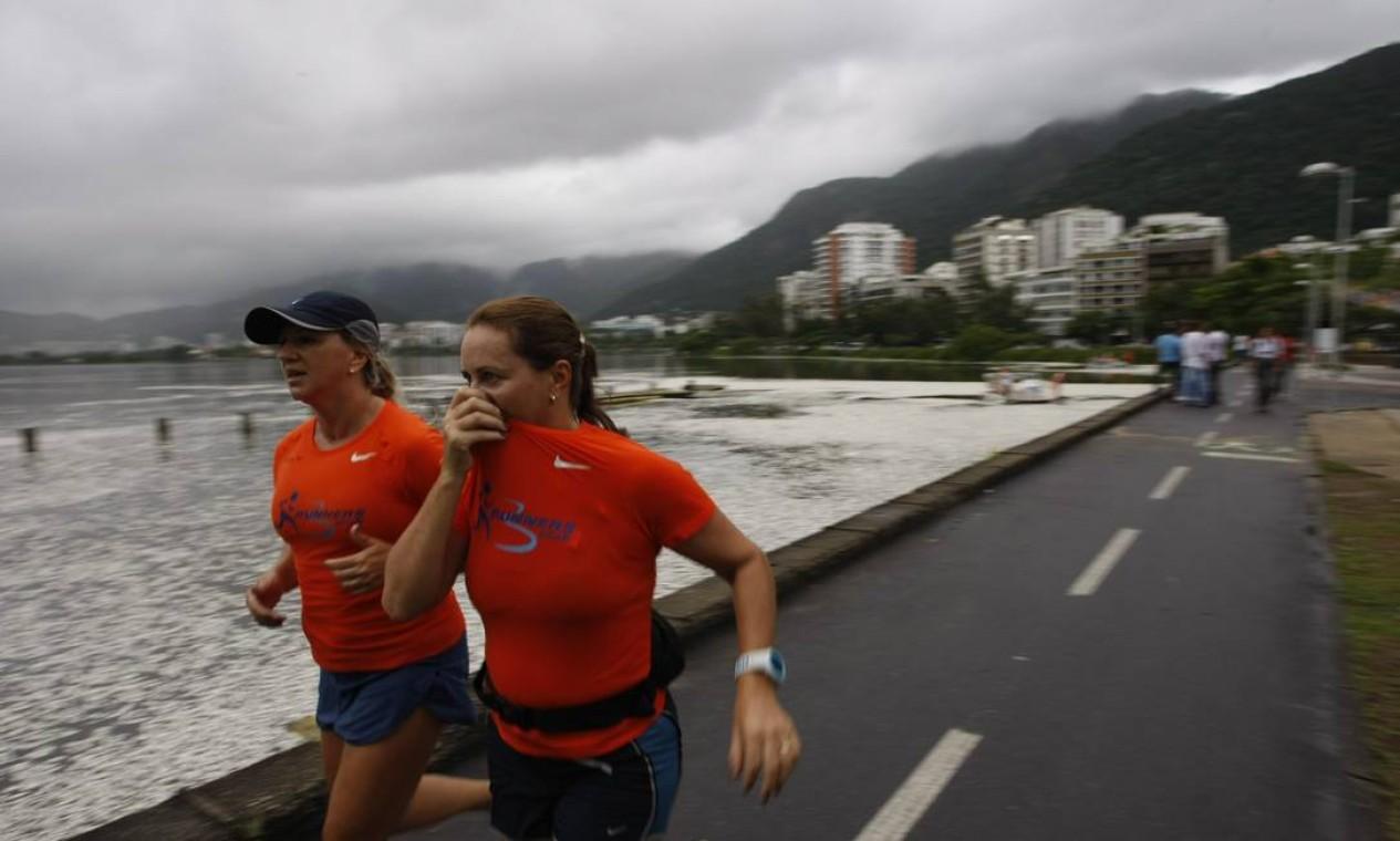 Corredora tapa o nariz ao passar pela Lagoa Rodrigo de Freitas na manhã desta quinta-feira Foto: Hudson Pontes / Agência O Globo