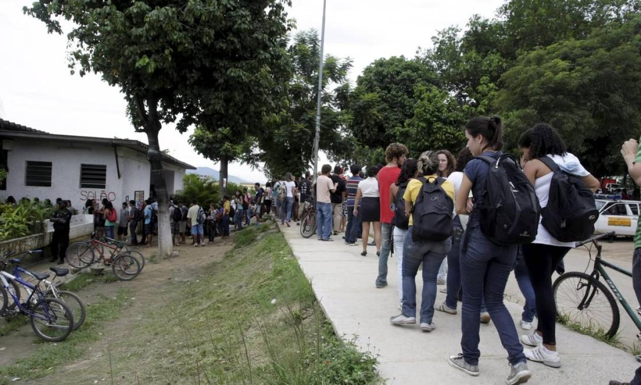 Quando chega a hora do almoço, os estudantes já sabem que vão enfrentar uma fila quilomêtrica, sob o sol ou sob a chuva Foto: Hudson Pontes / Agência O Globo