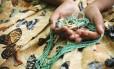 A., de 13 anos, segura sua guia sobre a saia baiana, símbolos do candomblé. Ela tem aulas obrigatórias de religião numa escola municipal de São João de Meriti