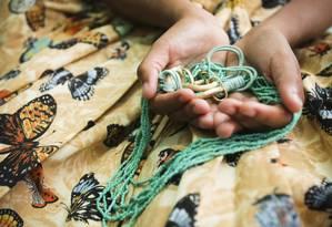 A., de 13 anos, segura sua guia sobre a saia baiana, símbolos do candomblé. Ela tem aulas obrigatórias de religião numa escola municipal de São João de Meriti Foto: Laura Marques