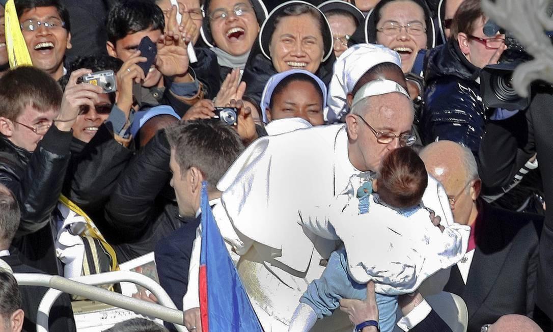 Autêntico. Francisco beija uma criança antes de sua entronização: para analistas, humildade do Papa não é artificial Foto: AP/19-3-2013