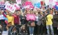 """Paris. No meio da multidão, uma mulher exibe cartaz onde se lê: """"Todos nascidos de um homem e de uma mulher"""""""