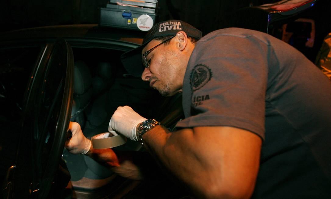 Papiloscopista da Delegacia de Homicídios do Rio recolhe digitais em carro usado em um crime Foto: Agência O Globo/ Arquivo