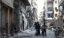 Crianças conversam com um menino segurando uma arma em uma área destruída na cidade de Homs, na Síria Foto: YAZAN HOMSY / REUTERS
