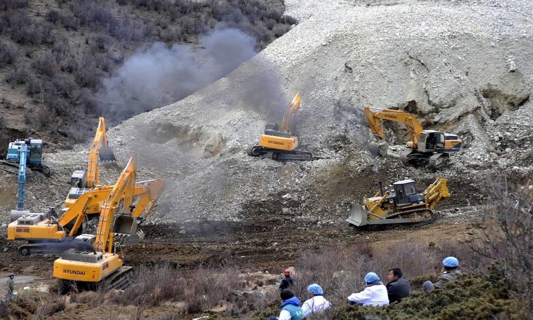 Escavadeiras removem pedras e lama após deslizamento de terra em Maizhokunggar, no Tibete Foto: Chogo / AP