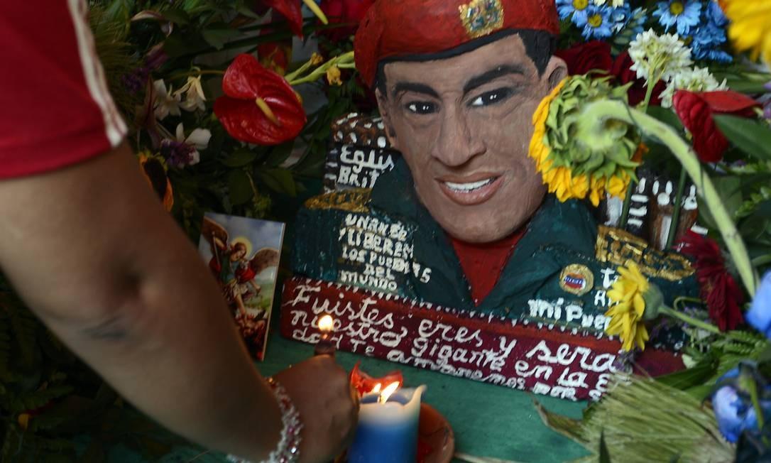 Mulher acende vela em altar para Hugo Chávez em Caracas Foto: JUAN BARRETO / AFP