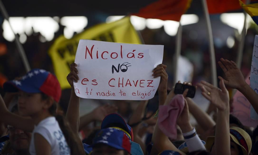 Crítica. Partidária de Capriles mostra cartaz afirmando que Maduro não é Chávez e não foi eleito Foto: JUAN BARRETO / AFP/26-3-2013
