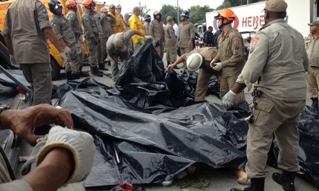 Bombeiros cobrem os corpos retirados do ônibus Gustavo Goulart