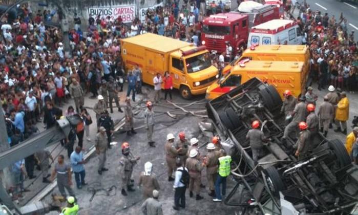 Muitas pessoas ficam em volta do ônibus acidentado, observando o trabalho dos bombeiros Foto de leitor