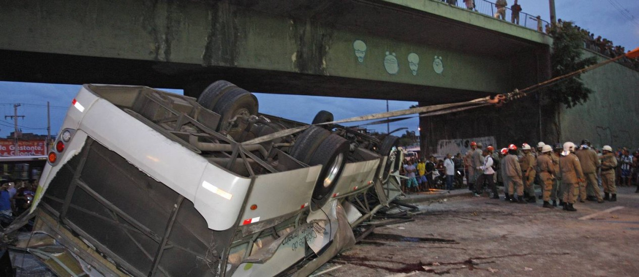 O ônibus caído sob o viaduto: grade não aguentou o impacto do veículo Foto: Márcio Alves / Agência O Globo