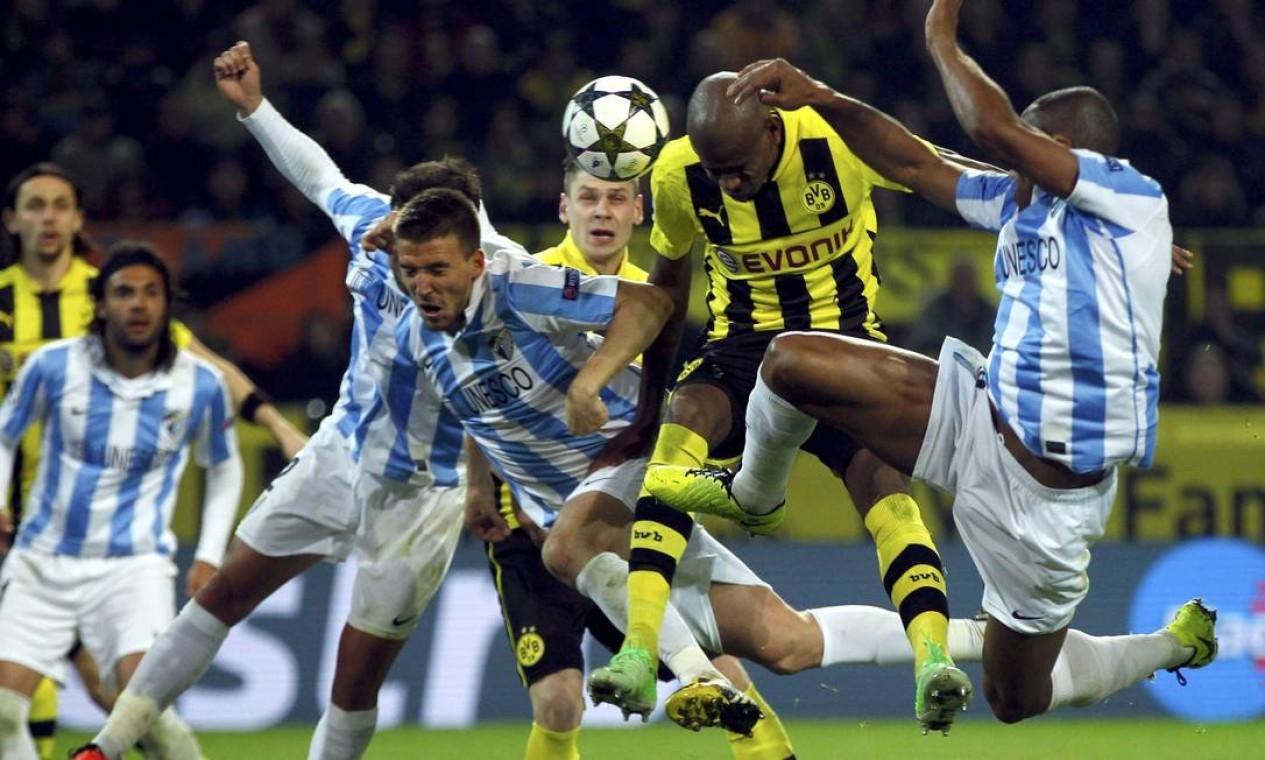 O brasileiro Felipe Santana, do Borussia Dortmund (ao centro), tenta uma cabeçada, cercado por zagueiros do Malaga Foto: INA FASSBENDER / REUTERS