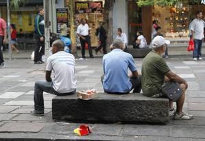 Mulher deixa restos de lanche em banco de rua Foto: O Globo / Marcelo Carnaval