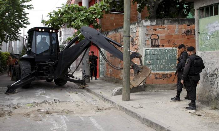Retroescavadeira é utilizada para retirar barricadas instaladas pelos bandidos Marcos Tristão / Agência O Globo