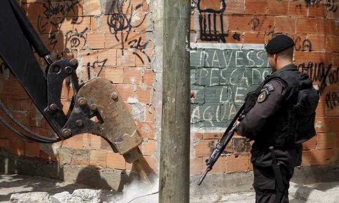 Policial observa o trabalho feito pela retroescavadeira Marcos Tristão / Agência O Globo