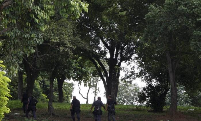 Policiais vasculham parque no alto da Ilha dos Macacos, dentro da Vila do João Marcos Tristão / Agência O Globo