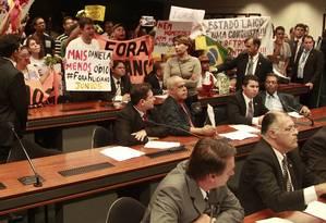 Manifestantes que defendem os direitos homossexuais e defensores de Marco Feliciano levantam seus cartazes no plenário da Comissão, que mais uma vez teve a sessão suspensa Foto: Jorge Willian / O Globo