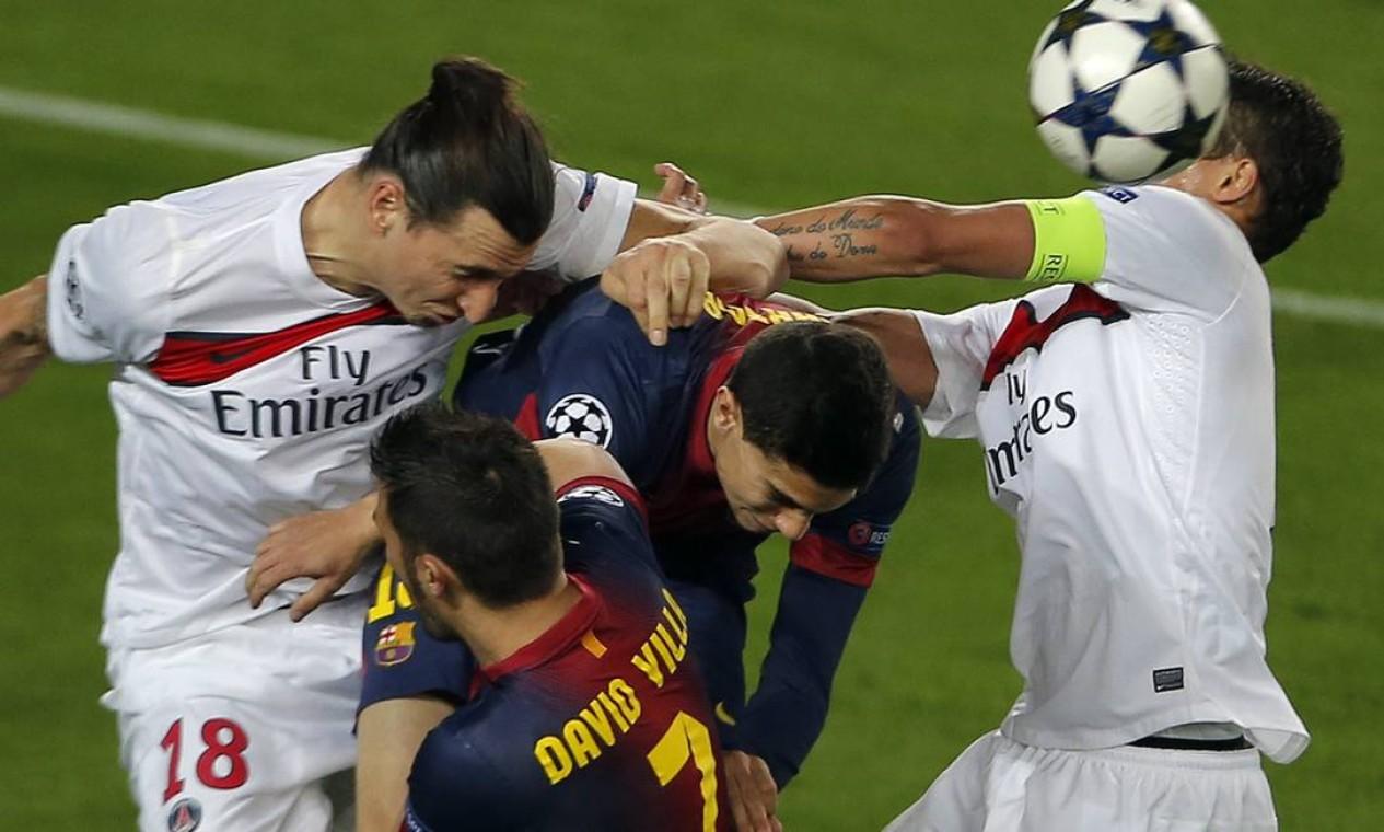 O brasileiro Thiago Silva, capitão do PSG, disputa a bola com com David Villa e Marc Bartra, do Barcelona Foto: JOSE JORDAN / AFP