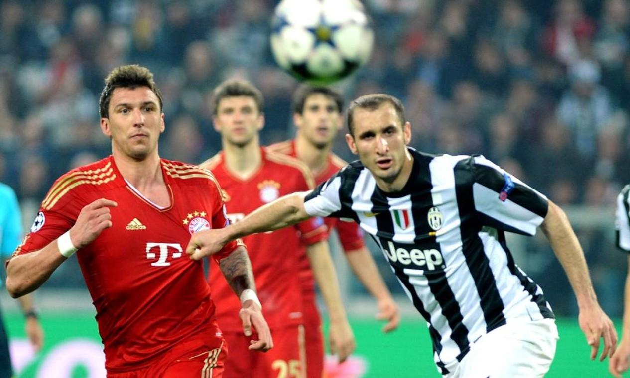 Giorgio Chiellini, da Juventus, puxa a camisa do croata Mario Mandzukic, do Bayern Foto: Massimo Pinca / AP