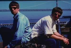 Liam (de azul) e Noel Gallagher, em 1997, mais de uma década antes da separação da banda Foto: Divulgação