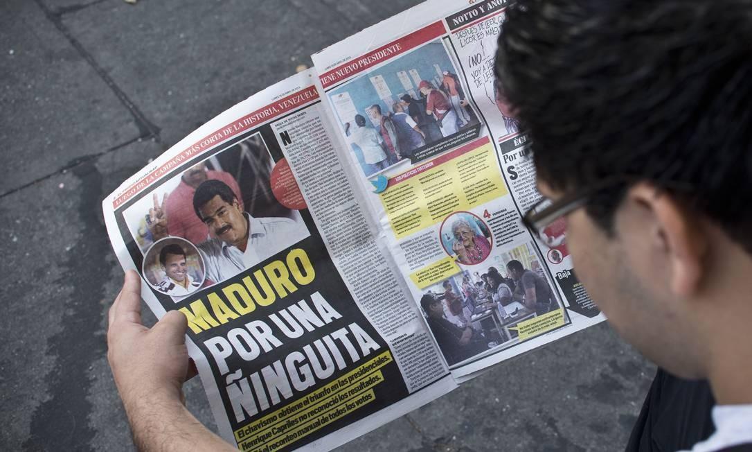 Um jovem lê um jornal que fala sobre a vitória apertada de Maduro Foto: Ronaldo Schemidt / AFP