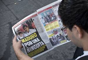 Venezuelano lê reportagem sobre a vitória de Maduro por margem estreita Foto: Ronaldo Schemidt / AFP