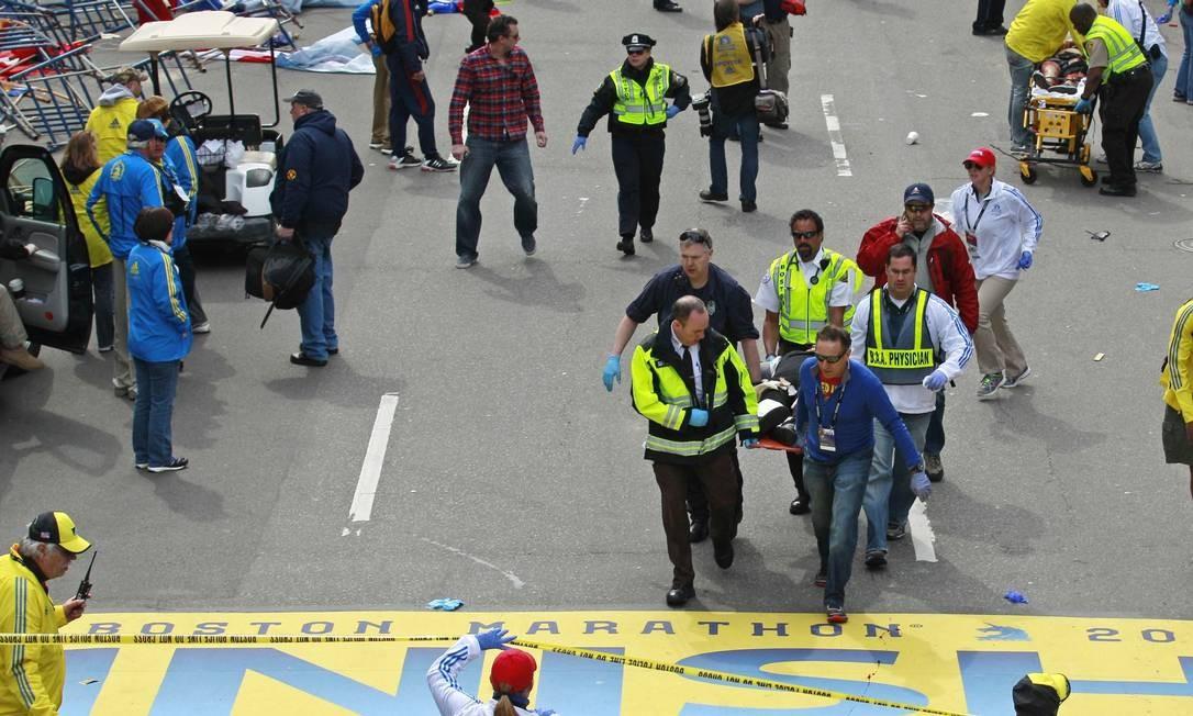 Feridos são retirados em macas, próxima à linha de chegada da corrida Foto: AP / AP