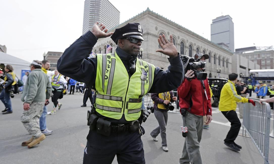 Um policial afasta os curiosos da área da explosão Foto: Charles Krupa / AP