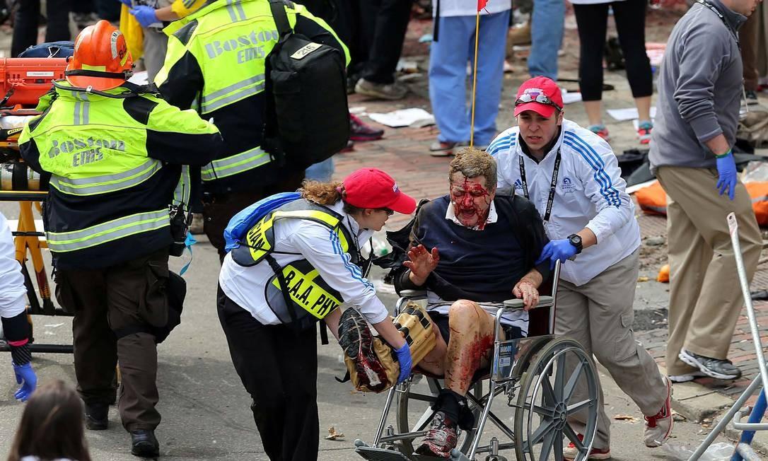 Homem ferido é socorrido após explosões na linha de chegada da Maratona de Boston Foto: David L. Ryan / AP