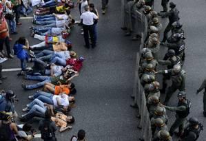 Manifestantes protestam diante de policiais e exigem a recontagem dos votos na Venezuela Foto: LEO RAMIREZ / AFP