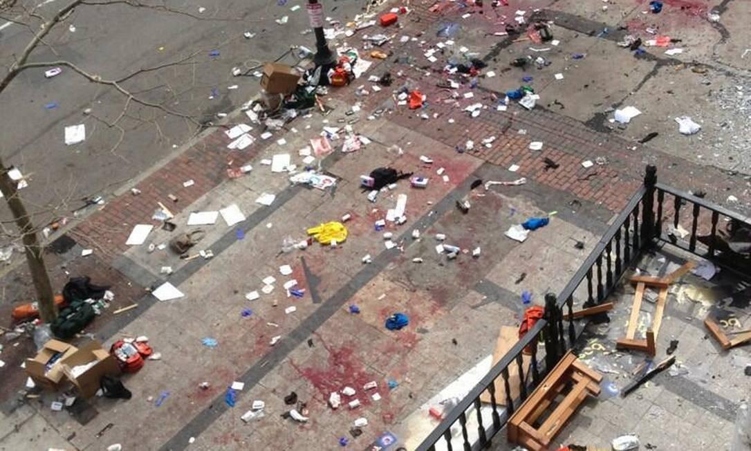 No local de uma das explosões, a calçada ficou inteiramente manchada de sangue Foto: Bruce Mendelsoh / AP