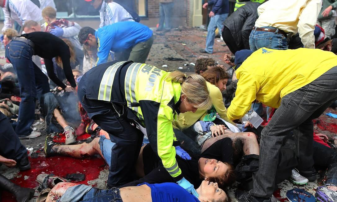 Feridos recebem os primeiros socorros após a primeira explosão em Boston Foto: John Tlumacki / Agência O Globo