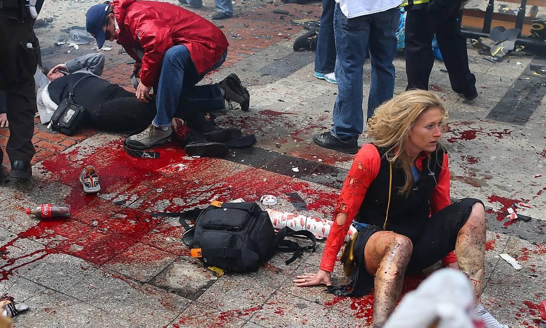 Feridos, em choque, logo após uma das explosões, aguardam atendimento Foto: John Tlumacki / The Boston Globe / Agência O Globo