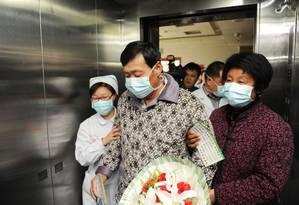 Um paciente que tinha contraído a gripe aviária é escoltado após sua recuperação e confirmação de alta de um hospital em Bozhou, na China Foto: STR / AFP